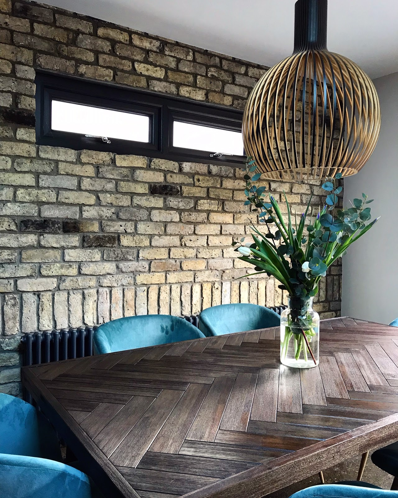 Exposed reclaimed brick wall in dining area